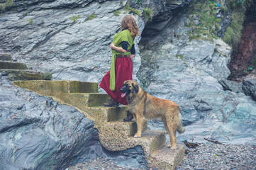 Woman carrying baby in sling with dog walking up steps