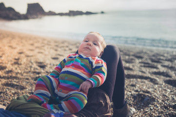 Young mother with baby relaxing on beach