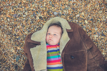 Baby wrapped up in coat on beach