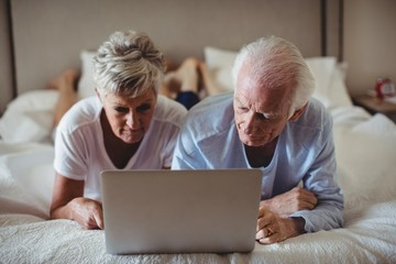 Senior couple lying on bed and using laptop