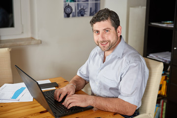 Man working on laptop at home on table
