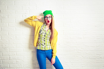 Funny Hipster Girl at White Brick Wall Background. Street Syle Teenage Going Crazy. Circling a First Finger by Her Temple. Trendy Fashion Outfit in Spring or Autumn. Copy Space.