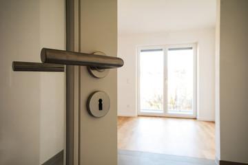 Neubau-Immobilie Umzug in neue Wohnung - Tür in modernes Wohnzimmer