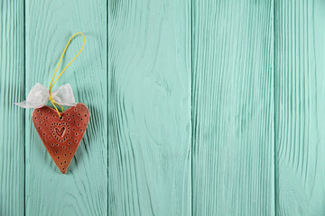 ceramic heart on a mint wooden background