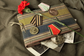 The composition of Victory Day.  Album with old military photos, carnation, medals.