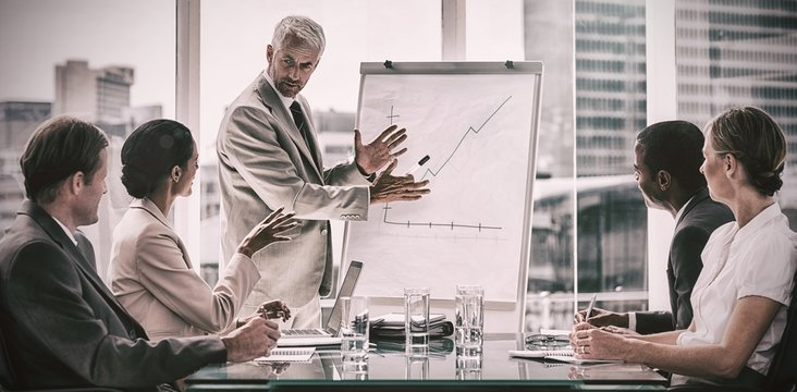 Businessman in front of a growing chart during a meeting