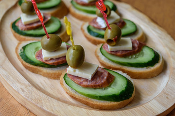 open canapés with cucumber, cheese, olives and pepperoni