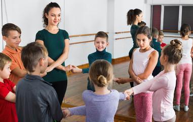 Boys and girls studying folk dance in studio