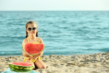 Cute girl eating watermelon on beach