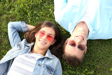 Beautiful young couple lying on green grass