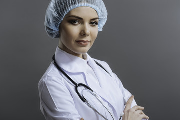 Delighted female doctor posing on grey background