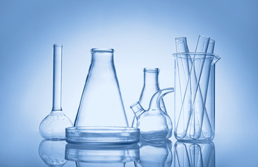 Test tubes and flasks on colour background