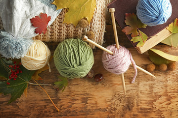 Knitting wool and needles on wooden table