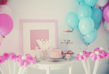 Tasty cake and sweets on table in room decorated for birthday party