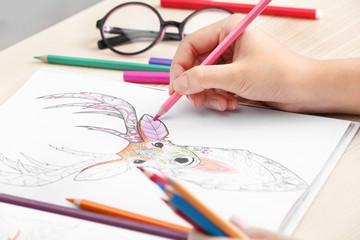 Woman coloring anti stress picture, closeup