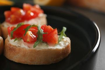 Tasty bruschetta on black plate
