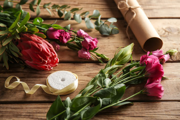 Beautiful flowers and packaging materials on wooden background