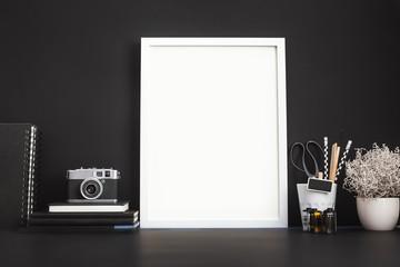 Black frame and camera on black desk