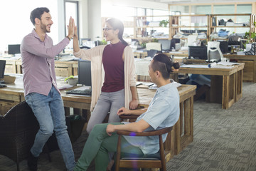 Architects high fiving in the office