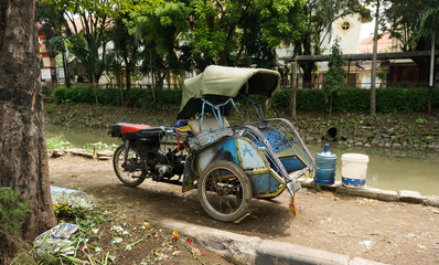 motorized tricycles parks beside a dirty river photo taken in Semarang Indonesia