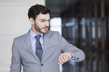 Confident businessman checking the time on wristwatch