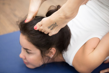 Portrait of beautiful young woman with tattoo on her foot meaning Wild kitty working out in fitness center, doing yoga or pilates exercise. Cheststand with backbend. Close up