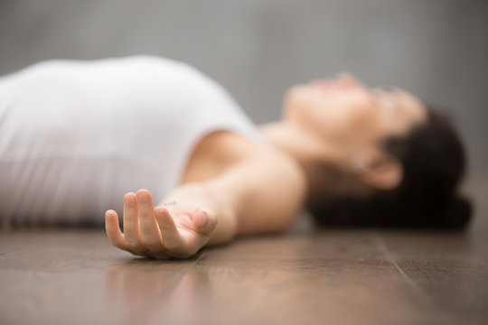 Beautiful young woman working out on wooden floor, resting after doing yoga exercises, lying in Shavasana Corpse or Dead Body Posture , relaxing. Close up, focus on hand