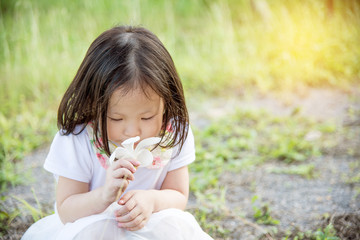 Little asian girl smelling flower in park