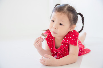 Little asian girl eating chocolate on the floor