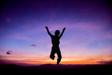 Silhouette of Child jumping up at Sunset