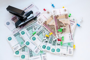 Multi-colored buttons, two stapler and money on a white background