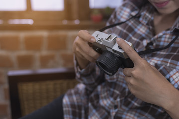 Portrait of hipster girl posing with retro camera wearing checke