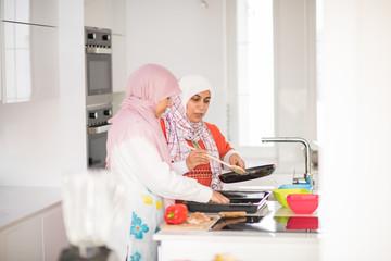 Muslim Arabic traditional woman in kitchen preparing food for lu