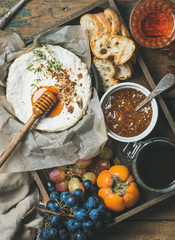Cheese, fruit and wine set. Camembert in small pan with nuts and herbs, grapes, persimmon, fig jam, honey, baguette slices and glass of rose wine over rustic wooden background, top view