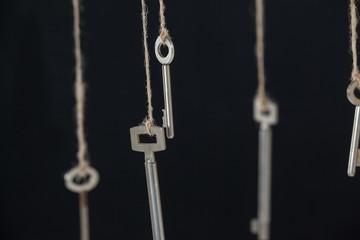 Keys hanging on strings against black background