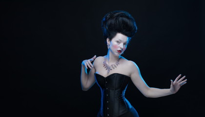 portrait of the actress brunette woman with high hair in a diamond necklace and dress with corset in old style on a black background