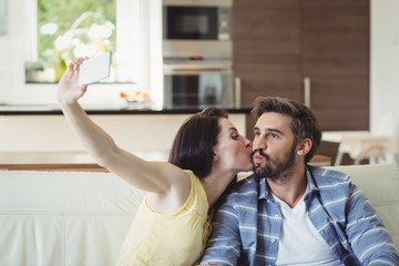 Romantic couple relaxing on sofa and taking a selfie