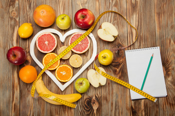 Fruit Diet, centimeter and plan on a wooden background
