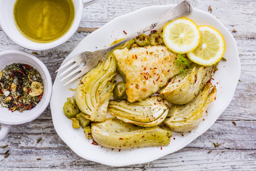 Baked fennel with herbs and olive oil served with fried fish.