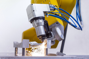 laser cutting of metal on robotic arm with sparks