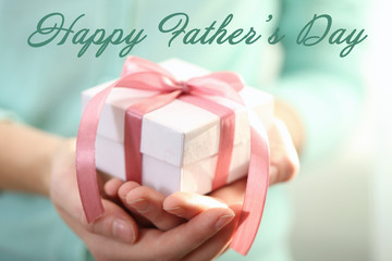 Woman holding gift box. Text HAPPY FATHER'S DAY on background