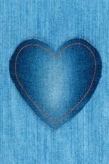Heart made of denim fabric lies on light denim