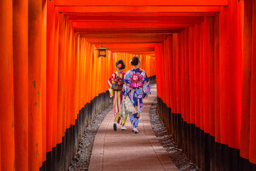 Women in traditional japanese kimonos walking at Fushimi Inari Shrine in Kyoto, Japan