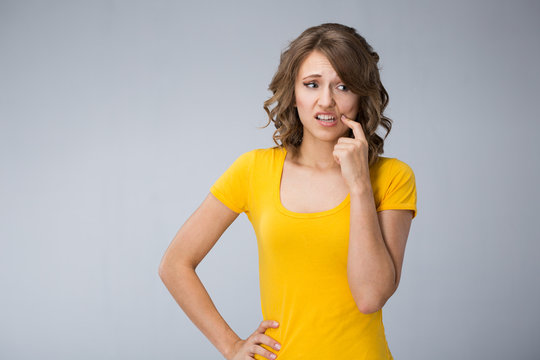 young woman wearing yellow shirt and jeans shorts  make faces