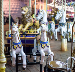 Old French carousel in a holiday park. Three horses and airplane on traditional fairground vintage . Merry-go-round with .