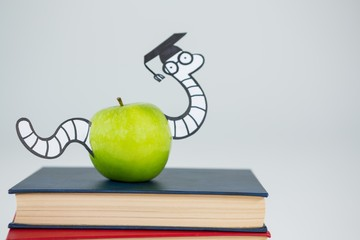 Conceptual image of books, apple and snake with graduate cap