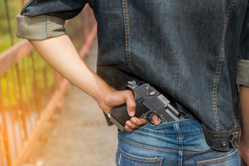 Man in jeans with hidden gun