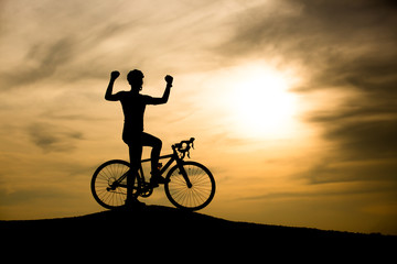 Silhouette of man on mountain bike at sunset