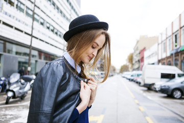 Fashionable young woman wearing hat and leather jacket