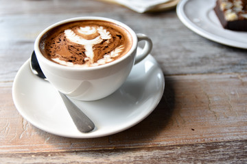 hot coffee cup on wooden table on brown background